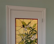 Stained glass piece inserted into a wood door.