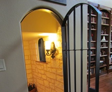 Custom made Wine Cellar to fit under stairs with Custom hammered iron gate