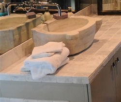 Antique stone vessel sink with stone tile counter/backsplash and wall mounted faucet