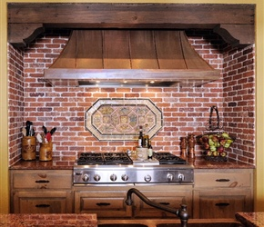 Kitchen: Custom built copper vent hood with knotty pine cabinets, brick backsplash and granite counters.